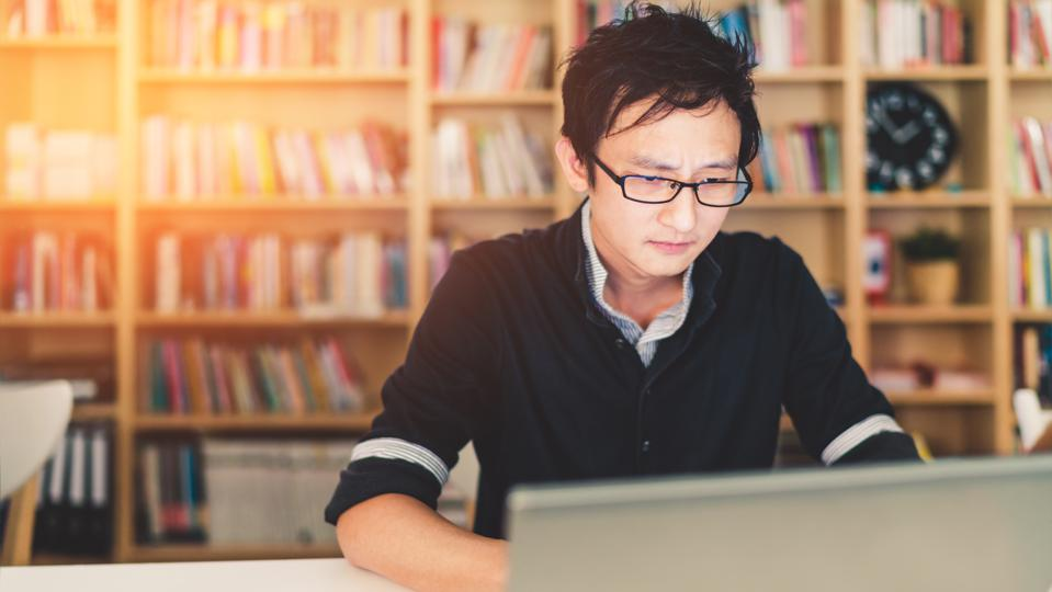 Asian man working on laptop with serious face