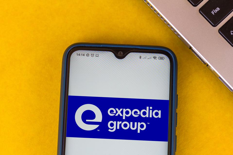In this photo illustration the Expedia Group logo seen...