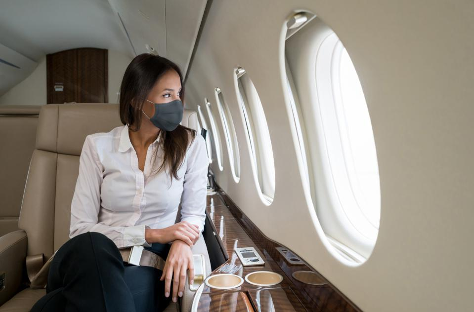 Business woman traveling in a private jet wearing facemask